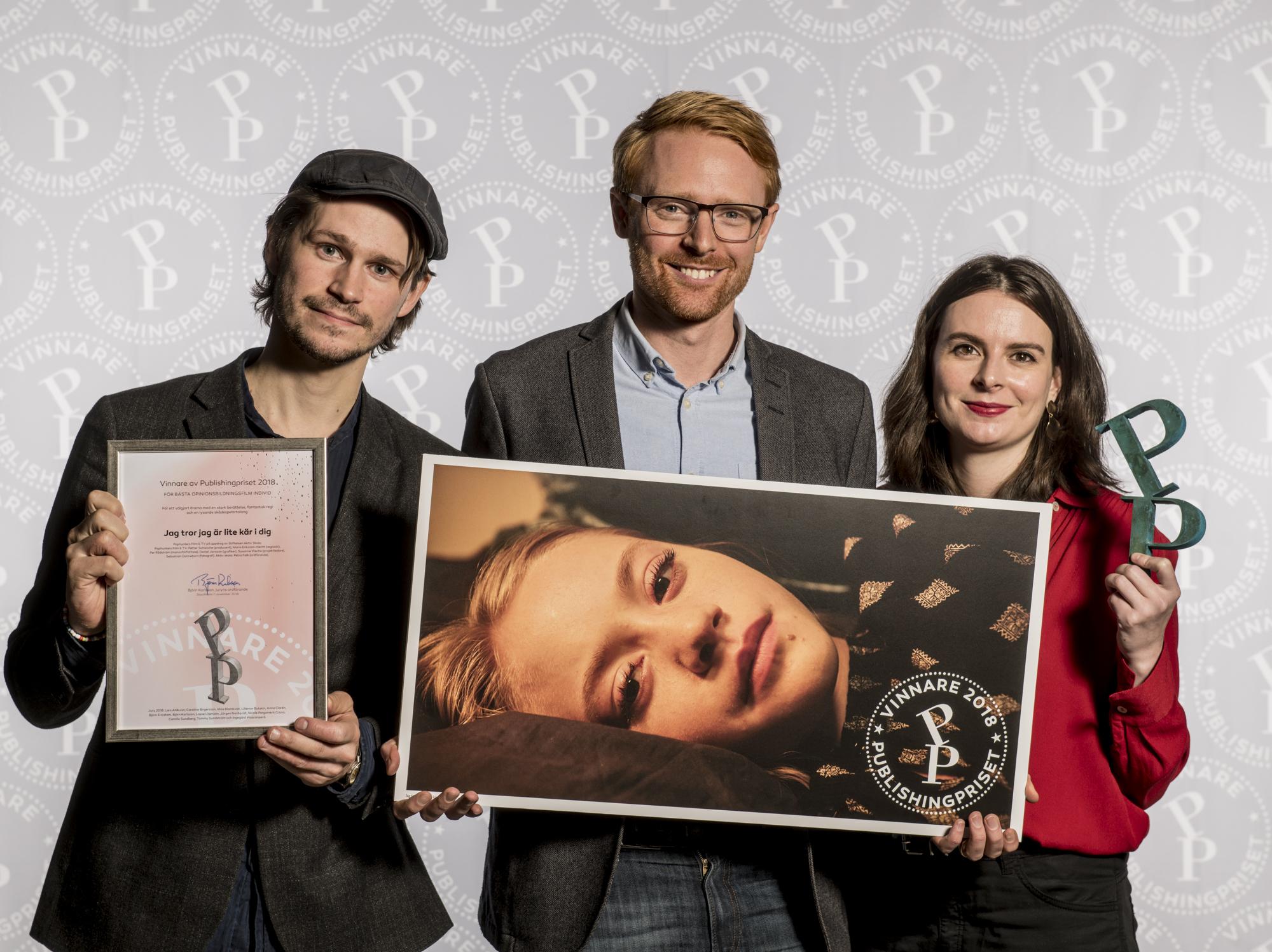 Filmens manusförfattare, producent och regissör poserar med publishingpriset